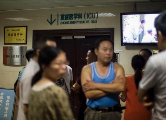 8月11日,事故受伤人员家属在当阳人民医院ICU病房门口等待伤员救治的消息。