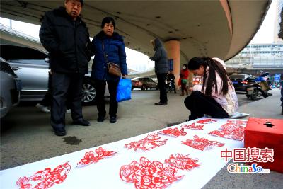 捐款账号;工商银行 户名:李西进(李婉君父亲)账号:621 226 171 700 380 3945 图为2016年1月5日,河南郑州,路人在围观李婉君义卖剪纸作品。(中国搜索 杨正华 文图)