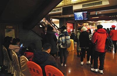 除夕夜,老字号全聚德前门店,等待翻台吃年夜饭的客人在门口排队等着叫号。