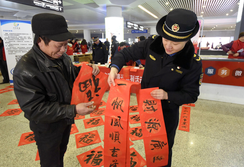 杭州城管队员火车东站送福写春联 温暖旅客回家路