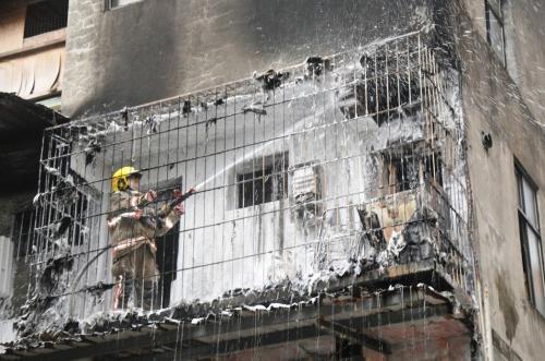台湾基隆市义七路一处民宅后阳台洗衣机起火烧毁。图片来源:台湾联合新闻网