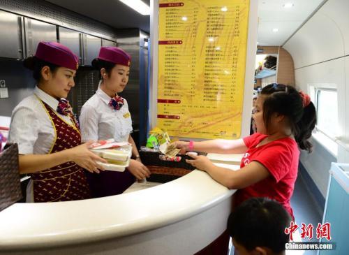 资料图:图为动车组乘务员正在向旅客出售盒饭。胡国林 摄