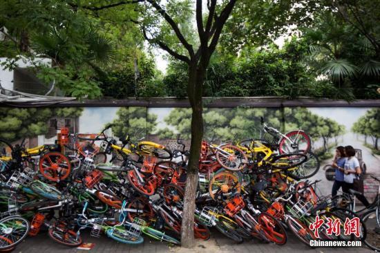 """9月19日,南京碑亭巷内,各种颜色的共享单车堆放在一起,色彩交织的""""叠罗汉""""景象令过往的市民侧目。 <a target='_blank' href='http://www.chinanews.com/'>中新社记者 泱波 摄"""